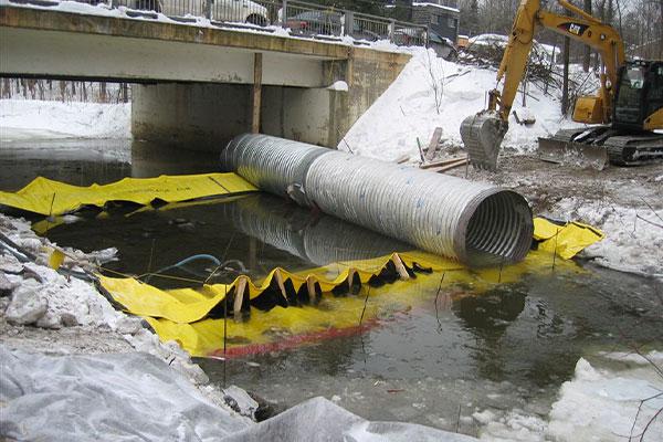 Installation af to Water-Gate © kufferter mod hale med bypassrør placeret på de fleksible dæmninger.