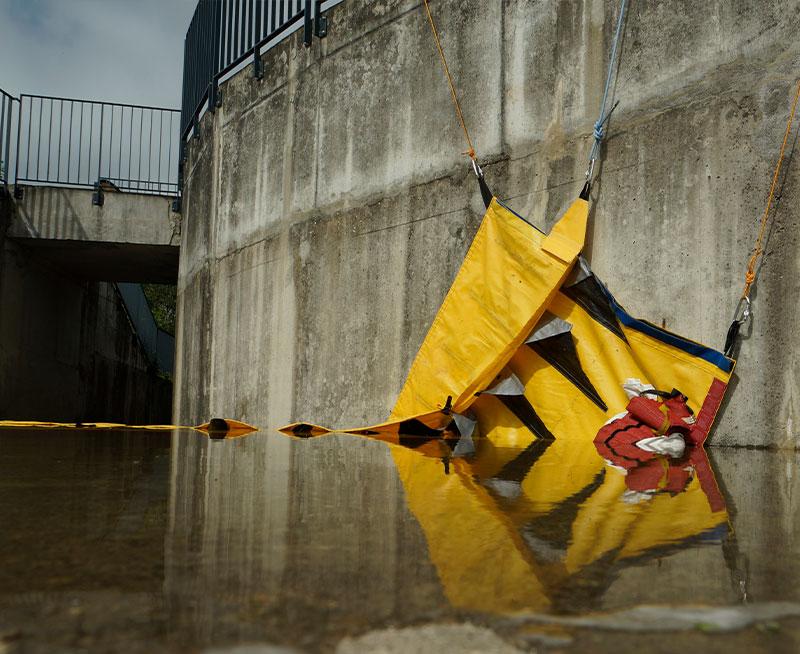 Fastgørelse af en Water-Gate© fleksibel kofferdam mod en væg med en åben vinkel.