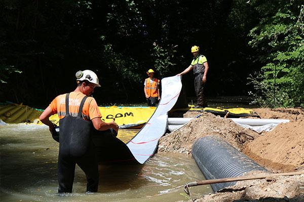 Den fleksible DP-3075 afgangsslange, 450 mm i diameter, er fastgjort til Water-Gate ©-dammen. Derefter ruller vi helt nedstrøms, inden vi fylder vandet.