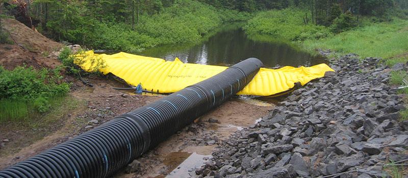 Fleksible Water-Gate © kasser til arbejde i floder. Aftagelig dæmning med bypass ved rørledning.